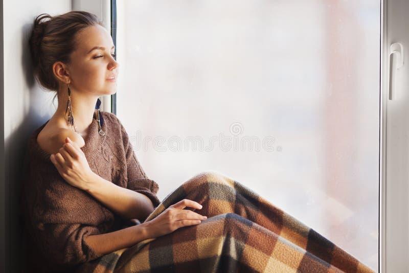 Vrouwenzitting op venstervensterbank met deken op haar knieën royalty-vrije stock foto