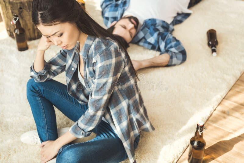 Vrouwenzitting op vloer dichtbij dronken vriend stock foto