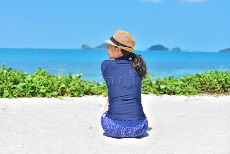 Vrouwenzitting op wit zand bij zonnige dag stock afbeeldingen