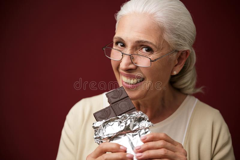 Vrouwenzitting over donkerblauwe achtergrond die chocolade eten stock fotografie