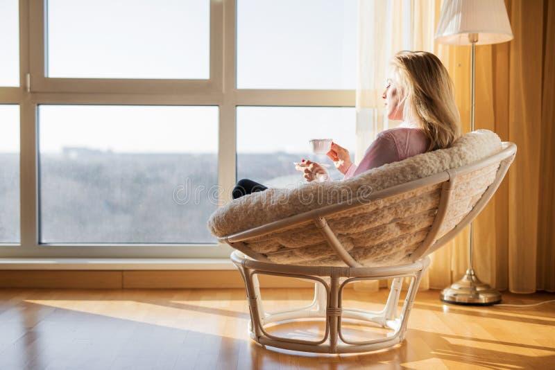 Vrouwenzitting in stoel en het drinken thee royalty-vrije stock foto