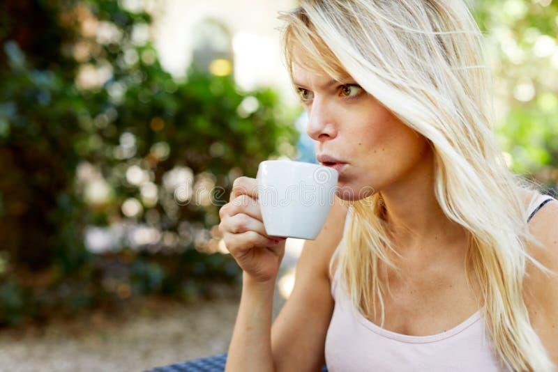 Vrouwenzitting in Ta-tuin en het drinken van een kop stock foto's