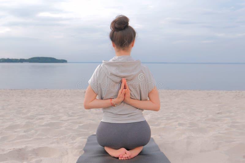 Vrouwenzitting terug op Yogamat en het doen van yoga uitrekkende oefening royalty-vrije stock fotografie