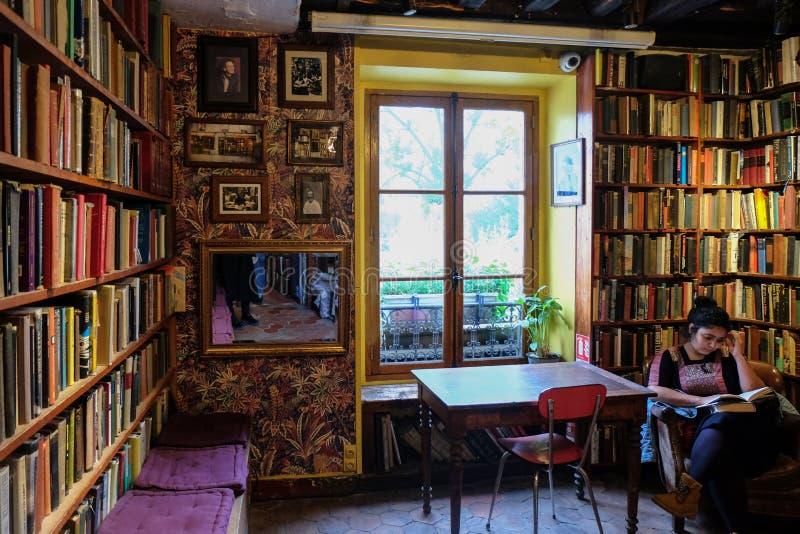 Vrouwenzitting voor plankenhoogtepunt van oude boeken Shakespeare & Bedrijf, Parijs, stock foto's