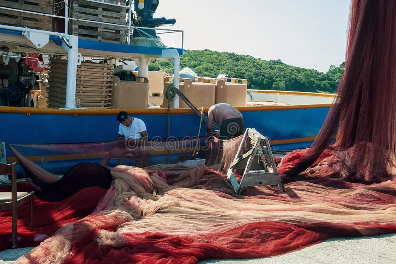 8 28 2012 Vrsar, Croatie Deux marins réparent le réseau déchiré sur le bateau Pêche en Mer Adriatique photos libres de droits
