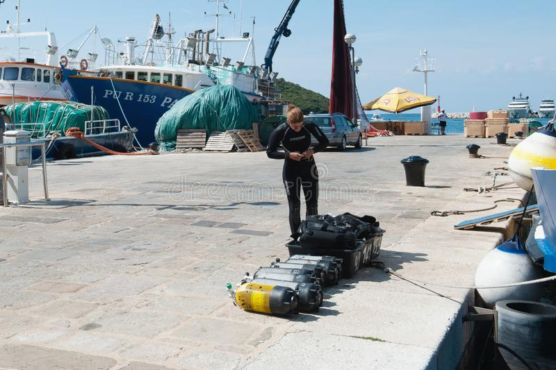 8 28 2012 Vrsar Kroati? De duiker controleert luchttanks vrij duiken op de pijler Volledige zuurstoftanks en duikuitrusting royalty-vrije stock afbeeldingen