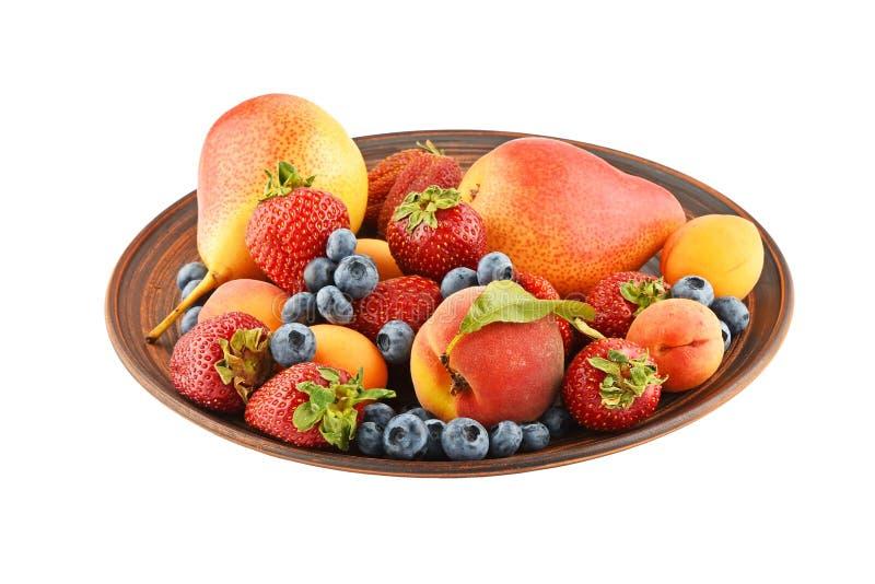 Vruchten en bessenmengeling in ceramische die plaat op wit wordt geïsoleerd royalty-vrije stock afbeelding