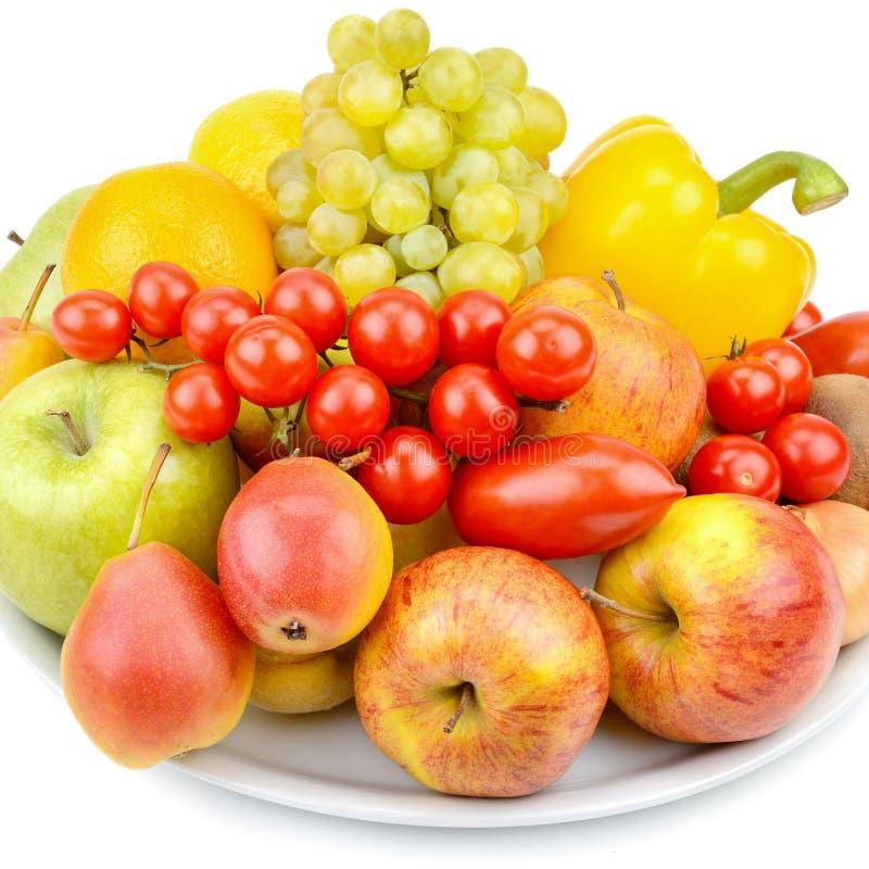 Vruchten en groenten op een schotel op witte achtergrond wordt geïsoleerd die stock foto