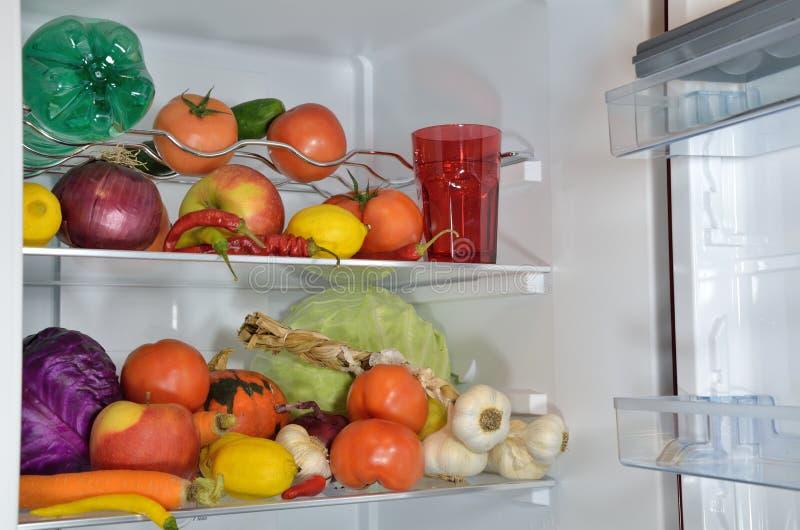 Vruchten, groenten en water in ijskast stock afbeelding