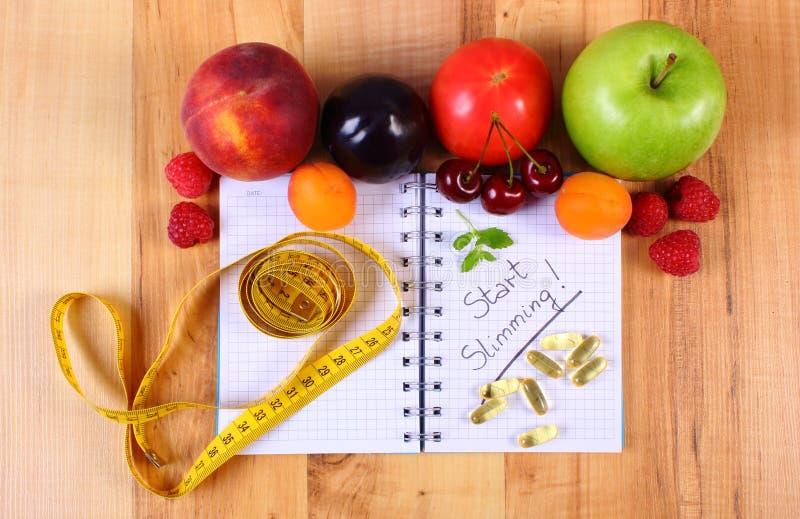 Vruchten, tablettensupplementen en centimeter met notitieboekje, vermageringsdieet en gezond voedsel royalty-vrije stock afbeeldingen