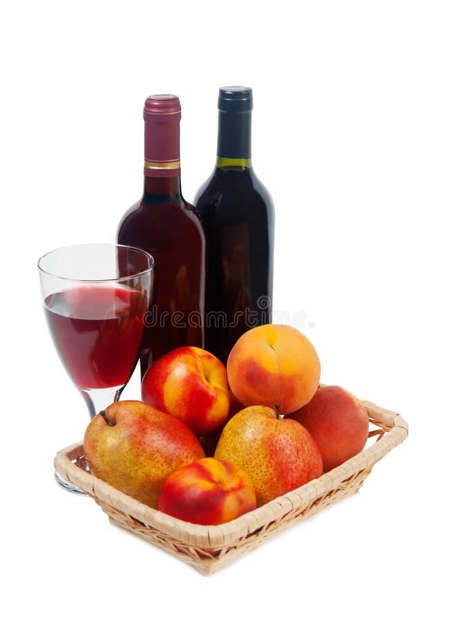 Vruchten, wijnflessen en een wijnglas op een witte achtergrond royalty-vrije stock afbeelding