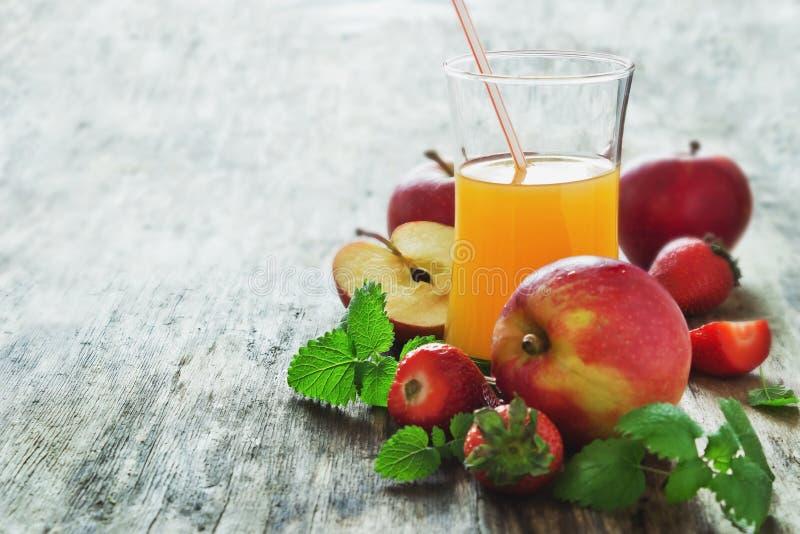 Vruchtensap, rijpe appelen en aardbeien stock afbeelding