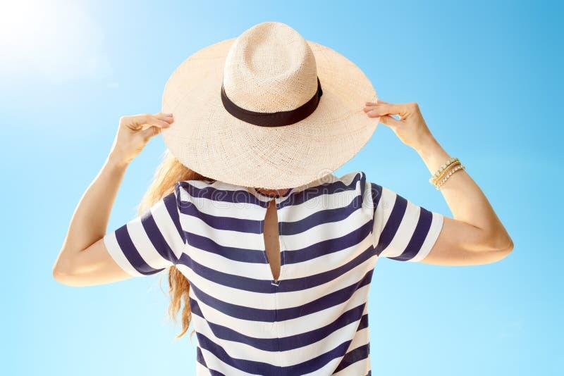 Vu par derrière la femme élégante dans le chapeau de paille contre le ciel bleu images libres de droits