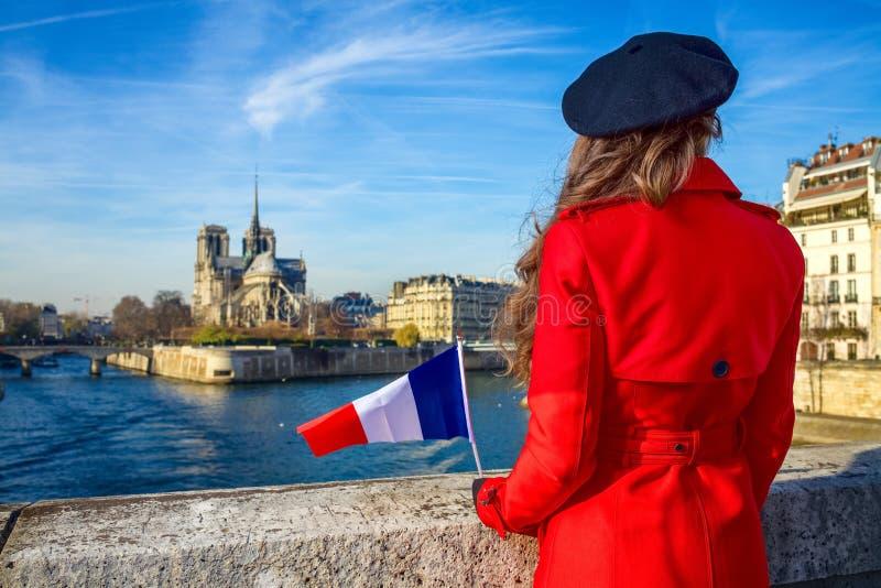 Vu par derrière la femme de voyageur avec le drapeau français à Paris photo libre de droits