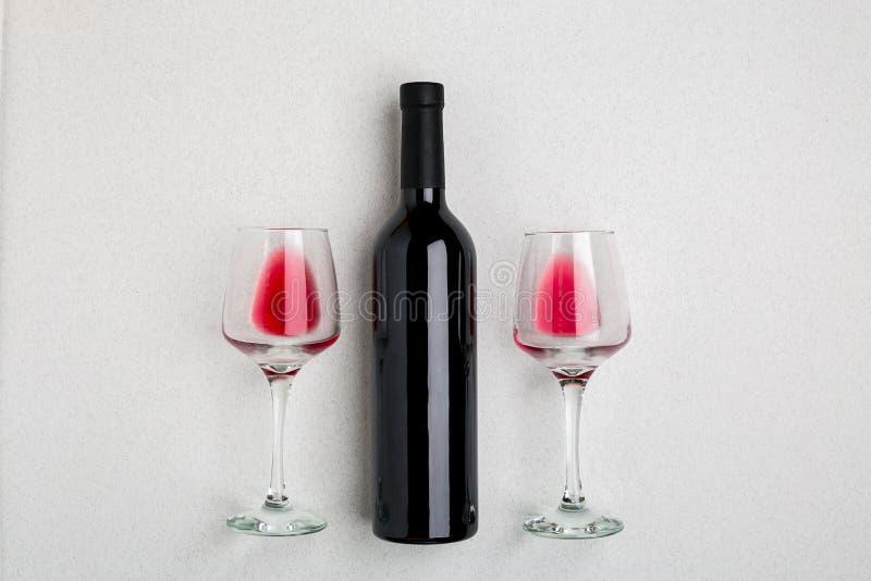 Vue à angles aérienne d'une grande bouteille de vin rouge, verres à boire sur le fond blanc photos stock