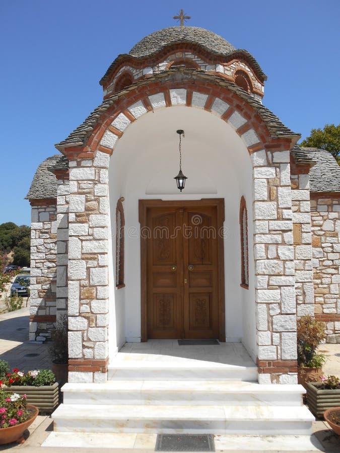 Vue à la porte de l'église blanche et brune d'Agios Nikolaos et d'Agia Anastasia au port de pêche d'Olympiada, Halkidiki photos libres de droits