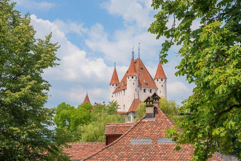 Vue à la tour historique du château de thun, au ciel bleu avec des nuages et aux branches vertes photo stock