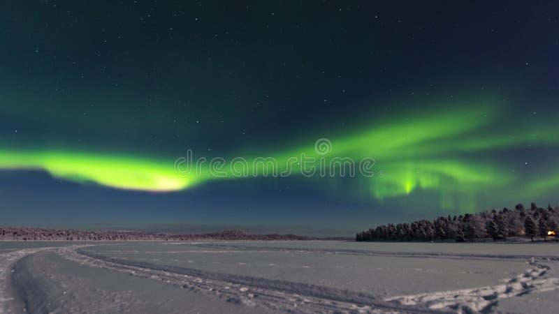 Vue à travers le lac vers une forêt comme hausse légère du nord dedans au ciel comme bande verte vive photo libre de droits