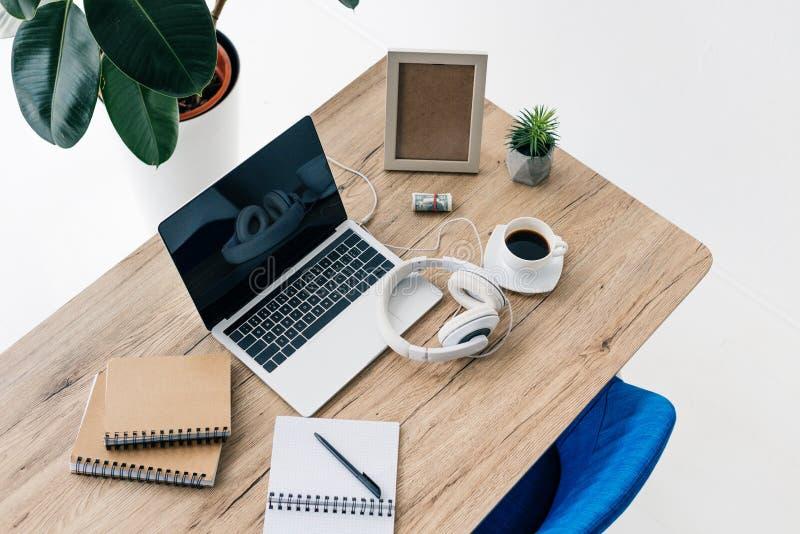 vue élevée d'ordinateur portable avec l'écran vide, écouteurs, manuels, cadre de photo, rouleau d'argent, usine mise en pot, tass images stock