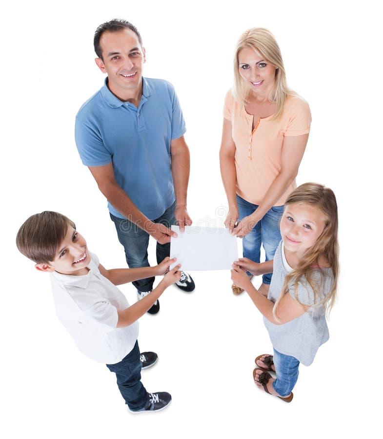 Vue élevée de famille retenant le papier blanc image libre de droits