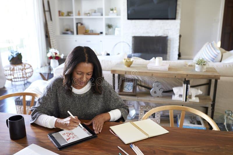 Vue élevée de la femme âgée moyenne d'Afro-américain s'asseyant à une table dans sa salle à manger utilisant un stylet avec une t photos stock