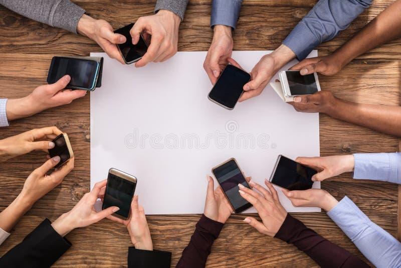 Vue élevée de main d'hommes d'affaires utilisant le téléphone portable photo stock