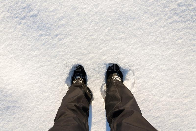 Vue étendue plate supérieure des pieds dans les bottes imperméables d'hiver dans la neige fraîche, pantalons noirs, fond blanc de photographie stock libre de droits