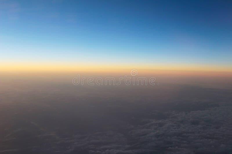 Vue étonnante d'avion sur le ciel, le soleil de coucher du soleil et les nuages photos libres de droits