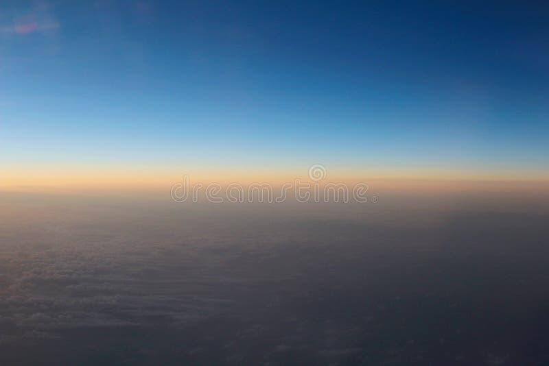 Vue étonnante d'avion sur le ciel, le soleil de coucher du soleil et les nuages images libres de droits