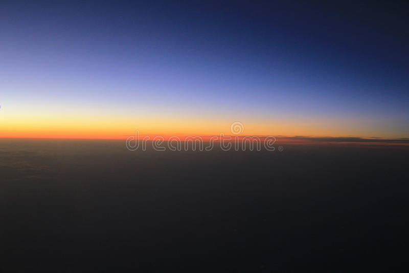 Vue étonnante d'avion sur le ciel, le soleil de coucher du soleil et les nuages photo libre de droits