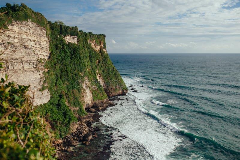 Vue étonnante de falaise raide et vue d'océan de temple d'Uluwatu en île de Bali La négligence falaise-frangée de littoral photo stock