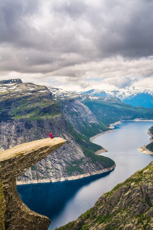 Vue étonnante de nature avec Trolltunga et une fille s'asseyant là-dessus L photos stock