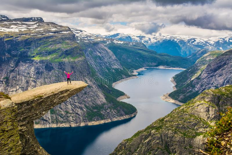 Vue étonnante de nature avec Trolltunga et une fille se tenant là-dessus photo stock