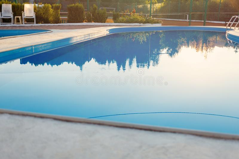 Vue étroite de piscine moderne au coucher du soleil à l'hôtel Lumière du soleil sur la surface Les vacances d'été, vacances, déte photographie stock libre de droits