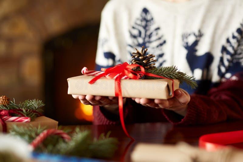 Vue étroite des mains de l'homme tenant et montrant le cadeau enveloppé fait main de Noël près de la cheminée Mâle dans le chanda photographie stock