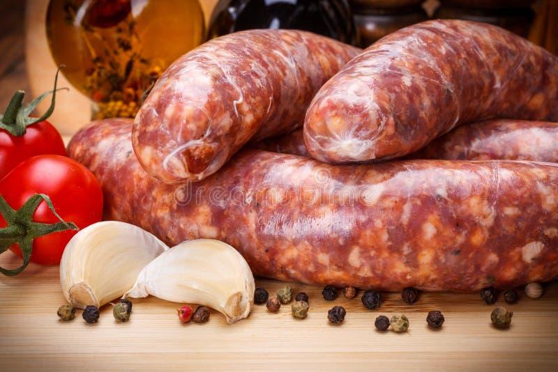 Vue étroite des saucisses épaisses de porc cru sur la planche à découper photographie stock