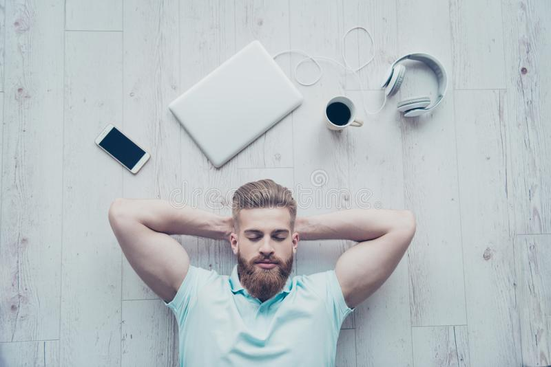 Vue aérienne d'homme calme dans les vêtements décontractés se trouvant sur le plancher photographie stock