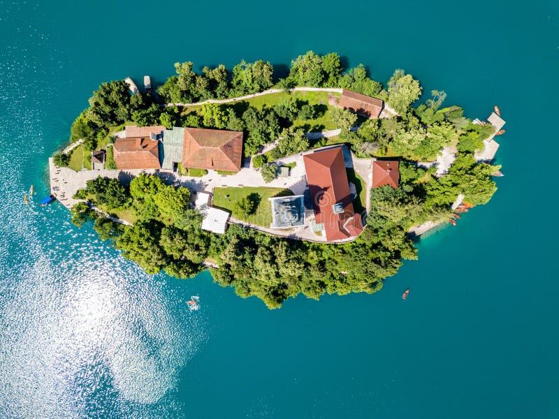 Vue aérienne d'otok d'île ou de Blejski Bled, acceptation d'église de Mary avec une tour et flèche, sur le lac saigné par montagn image libre de droits