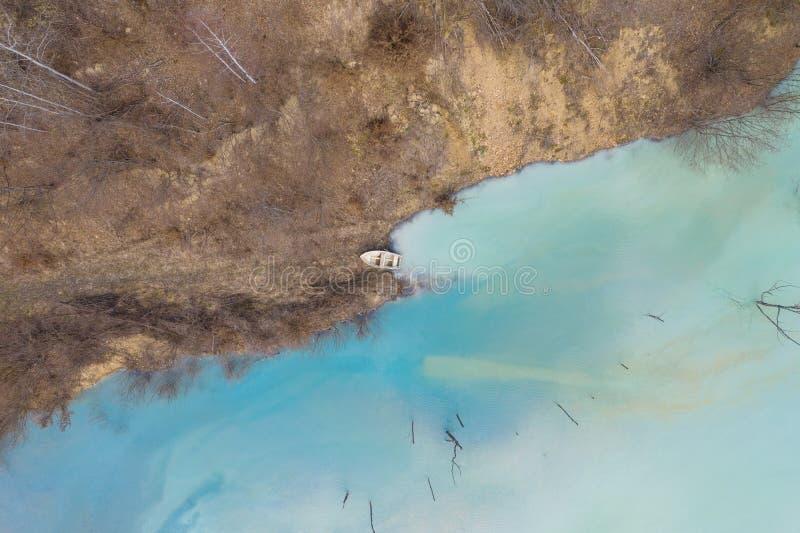 Vue aérienne d'un bateau dans un lac de turquoise souillé avec du cyanure photo libre de droits
