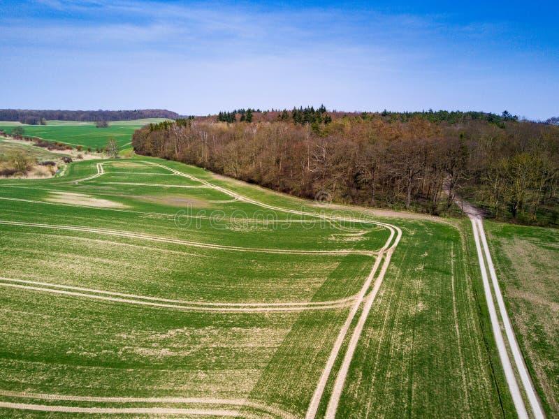Vue aérienne d'un champ agricole pendant le ressort - voies de tracteur image stock