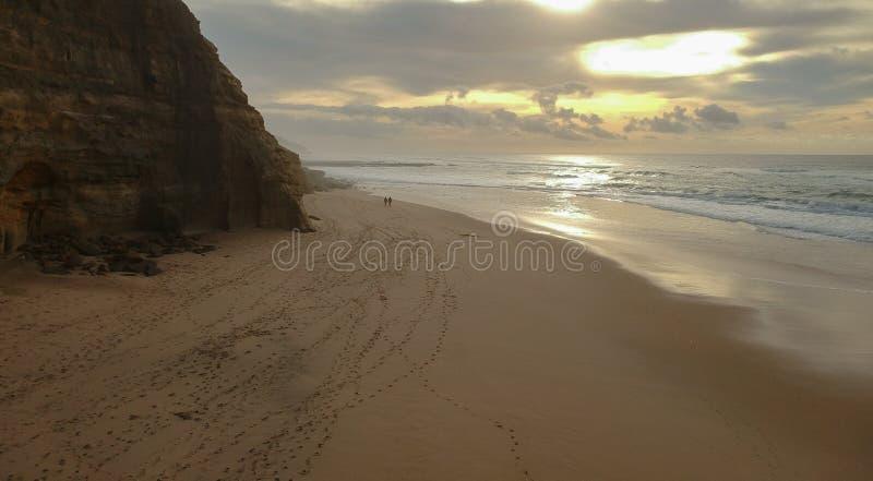 Vue aérienne d'un couple marchant la plage sablonneuse au coucher du soleil avec une falaise étonnante photo libre de droits