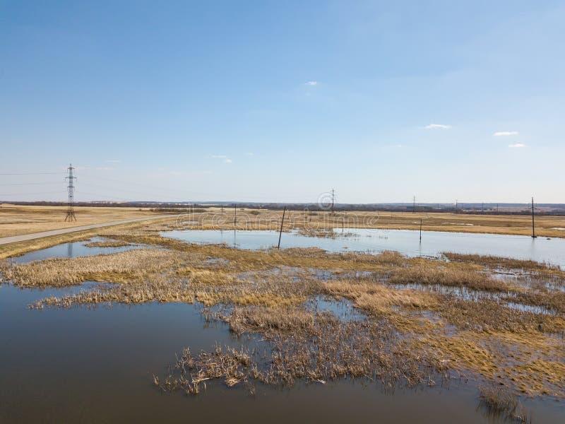 Vue aérienne d'un marécage près d'une route avec une route goudronnée pendant une inondation de ressort, qui inonde et brouille l photographie stock libre de droits