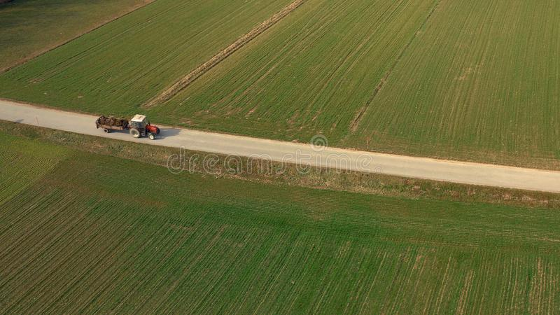 Vue aérienne d'un tracteur et d'une remorque rouges supportant une charge d'engrais sur la route image stock