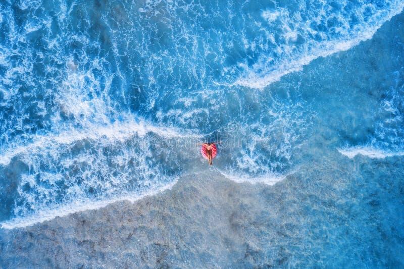 Vue aérienne d'une natation de jeune femme avec l'anneau de bain de beignet image stock