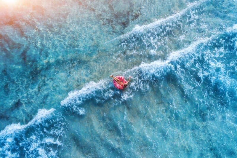 Vue aérienne d'une natation de jeune femme avec l'anneau de bain de beignet images stock