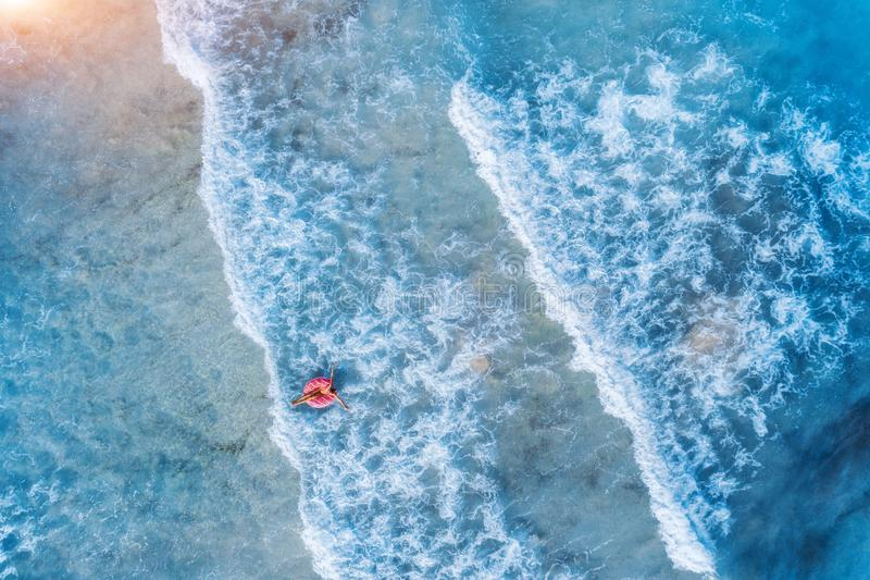 Vue aérienne d'une natation de jeune femme avec l'anneau de bain de beignet photographie stock