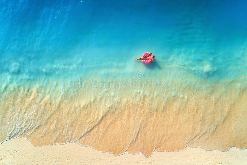 Vue aérienne d'une natation de jeune femme avec l'anneau de bain de beignet image libre de droits
