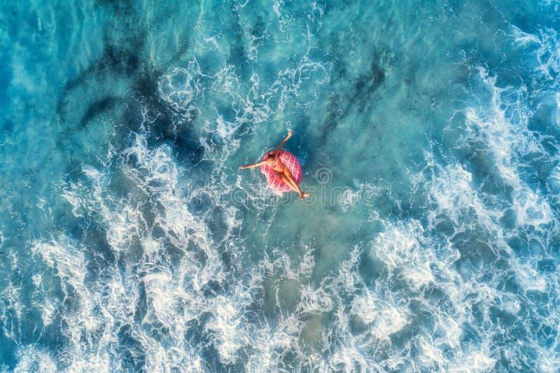 Vue aérienne d'une natation de jeune femme avec l'anneau de bain de beignet photos stock