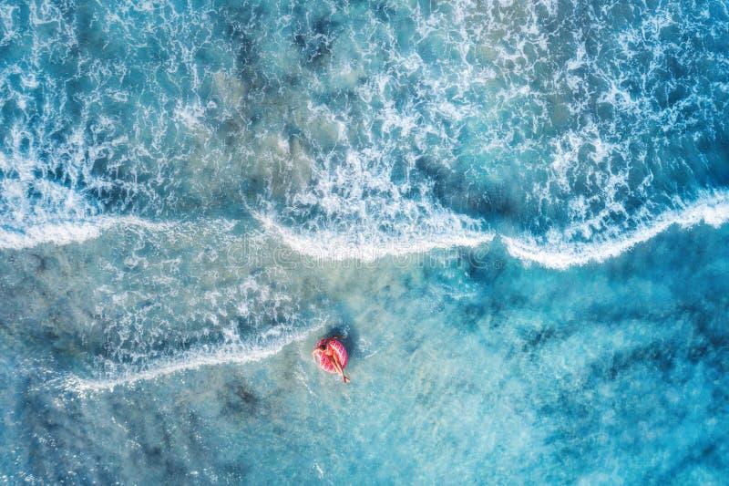 Vue aérienne d'une natation de jeune femme avec l'anneau de bain de beignet photos libres de droits