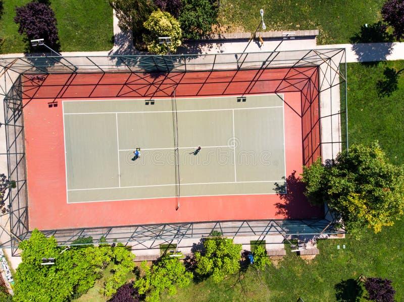 Vue aérienne de bourdon de court de tennis dans le jardin avec des joueurs jouant le tennis photographie stock